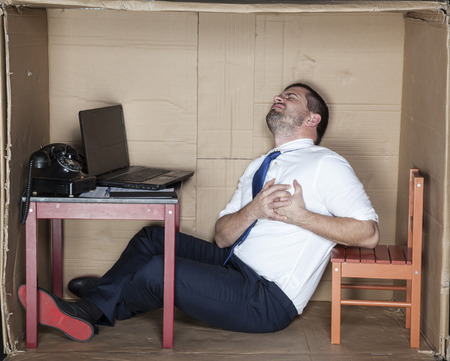 unease: Businessman gets a heart attack at work Stock Photo