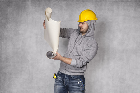 awkwardness: Worker reading building plans Stock Photo