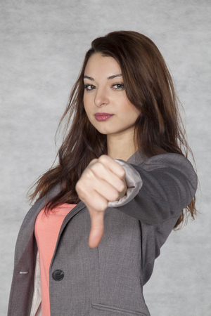 indignant: Young businesswoman shows thumb down