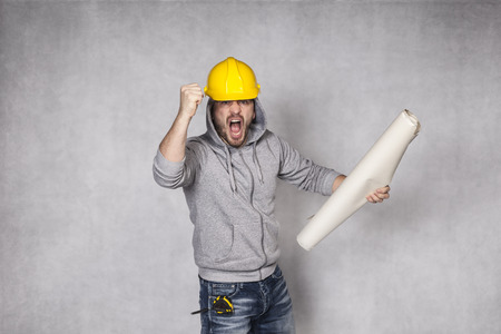 awkwardness: angry builder holding blueprints in hand Stock Photo