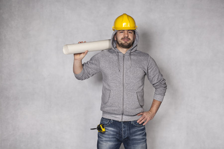 awkwardness: builder is thriving on a gray background Stock Photo
