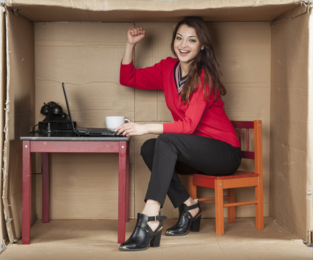 cramped space: business woman raises her hand up in a gesture of victory Stock Photo