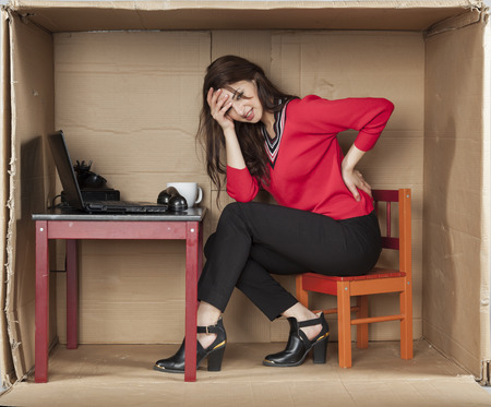 cramped space: grimace of pain on his face business woman Stock Photo