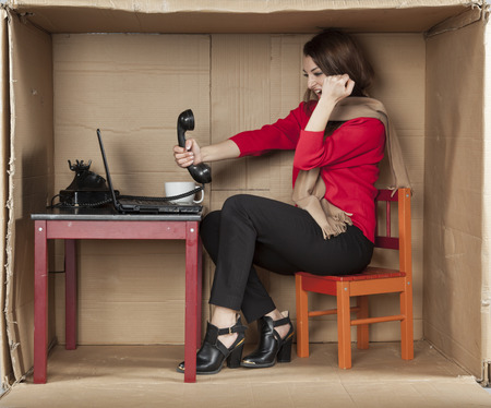 cramped: business woman shouting into a phone, office situation
