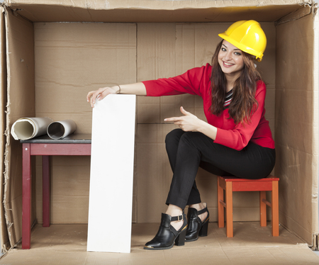 cramped: serious lady architect in office, pointing to the copy space Stock Photo