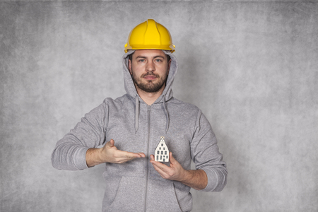 awkwardness: Worker holds a house in his hand