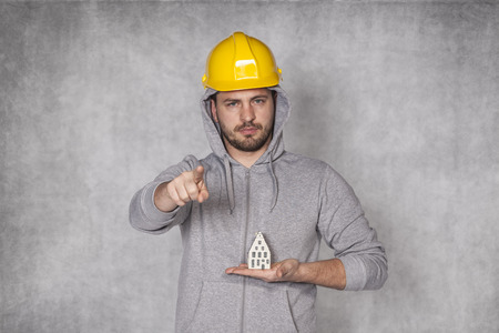 awkwardness: Worker holds a house in his hand and pointing at you