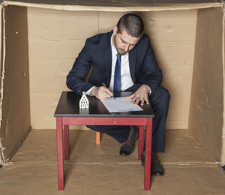 careerist: businessman signs a contract insurance on the house