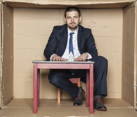 careerist: businessman and his desk with a model home