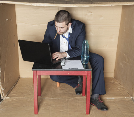businessman working at his computer: businessman with a cigarette in his mouth working on a computer