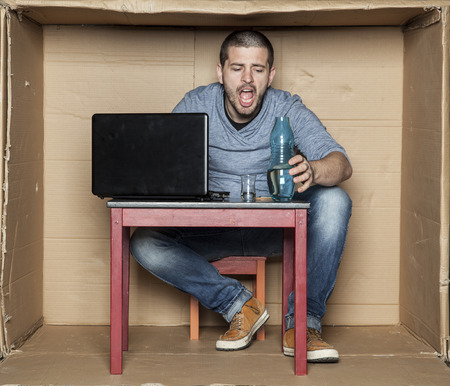 idiot box: student grabs the bottle of alcohol Stock Photo
