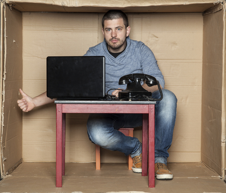 cramped space: young office worker shows thumbs up under the desk