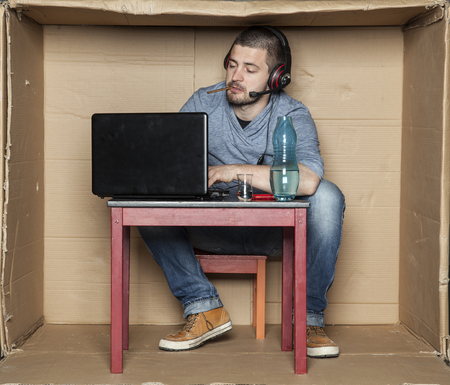 idiot box: intern with a cigarette in his mouth and alcohol on the table Stock Photo