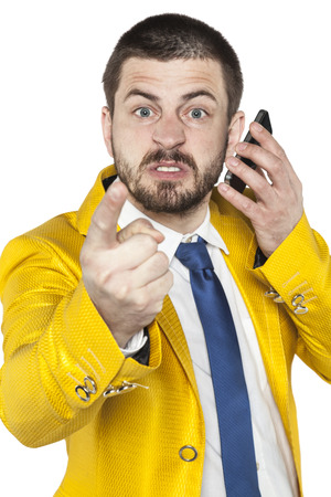 threatens: not happy businessman talking on the phone and threatens finger