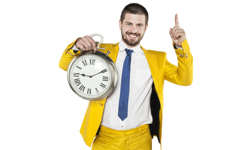 businessman in a gold suit holding a clock in his hands