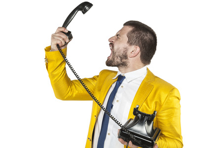 denunciation: angry businessman screaming to the telephone handset