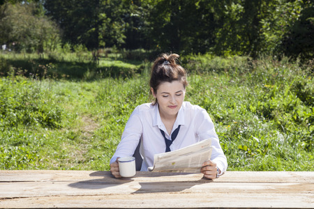 careerist: focused business woman while reading the morning newspaper
