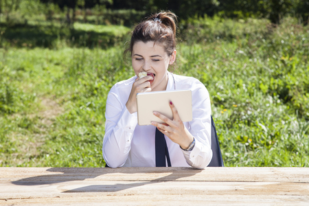 availability: business woman eating an apple and reading messages