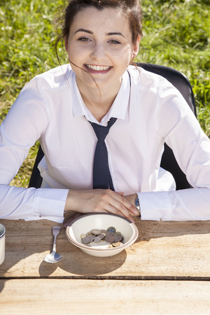 Joyful business woman sitting in front of a plate with money Stock Photo