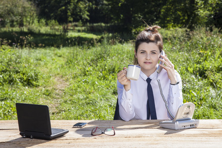 business woman talking on the phone and drinking coffee