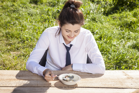business woman eats breakfast in the open air, money in a plate Stock Photo