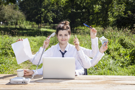 multitasking business woman sitting in the office Stock Photo