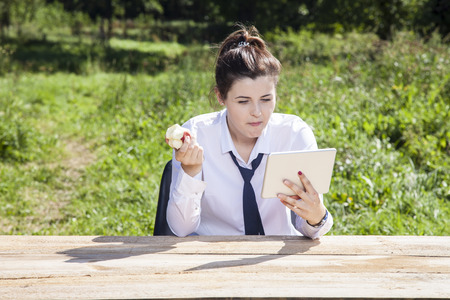 focused business woman eating an apple and reading messages