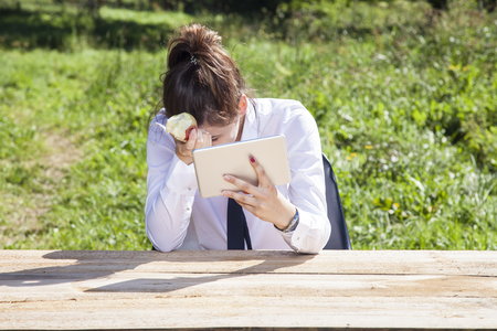 depressed business woman eating an apple and reading messages Stock Photo