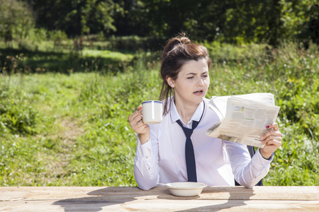 careerist: business woman drinking coffee and reading the newspaper, surprised face