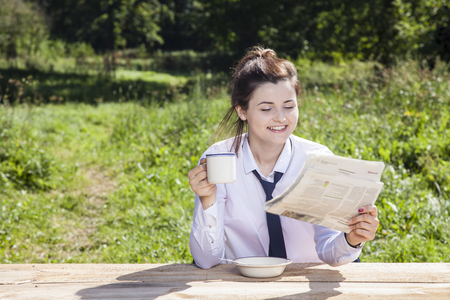 careerist: business woman reading a newspaper while drinking coffee