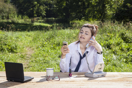 careerist: business woman talking on the phone, the other holds in her hand