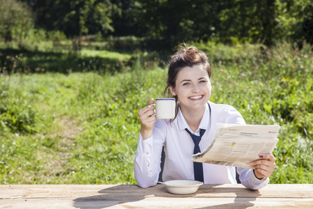 careerist: young business woman reading a newspaper while drinking coffee