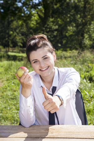 business woman eating an apple, thumb up