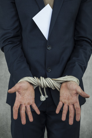 bribes: businessman hands are tied from bribes