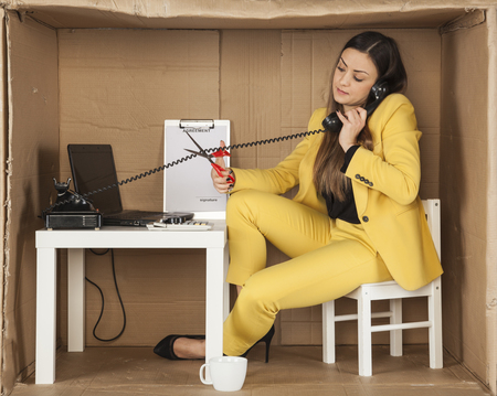 cramped: call center employee cuts the cable from the phone handset, during a telephone conversation Stock Photo
