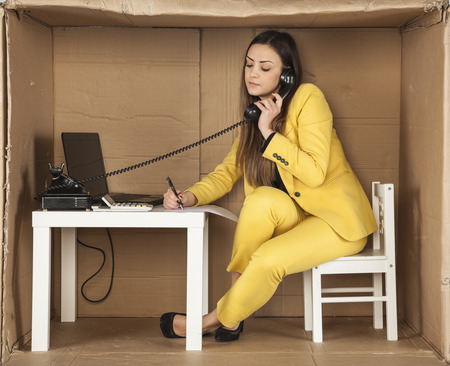 cramped space: business woman talking on the phone and making notes at one time Stock Photo
