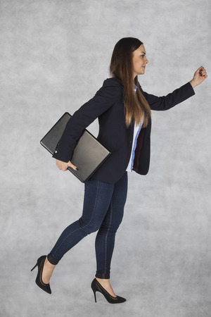business woman ready to run, laptop in hand Stock Photo