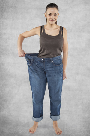 Girl in old pants, lost weight Stock Photo