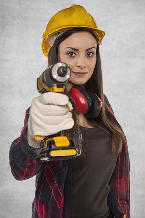 resourcefulness: Female worker holding an electric screwdriver