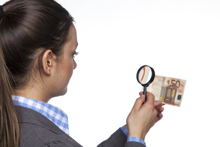 arrears: Young business woman checks the authenticity of money on white background