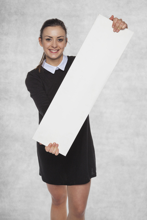 Smiling fashion woman holding a blank billboard, space for your AD