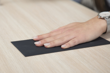get tired: Hand on a black envelope, bribe on the desk Stock Photo