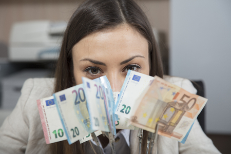 Business woman hides behind money Stock Photo