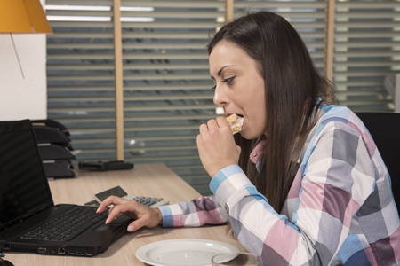 energy needs: The secretary eats the sandwich and works on the computer