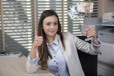 Business woman shows a statuette of money, success in business, thumb up