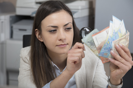 Business woman checking the authenticity of money Stock Photo