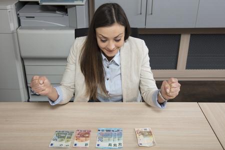 Happy business woman spreads money on a desk