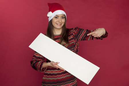 Smiling young woman holding copy space for Christmas sales