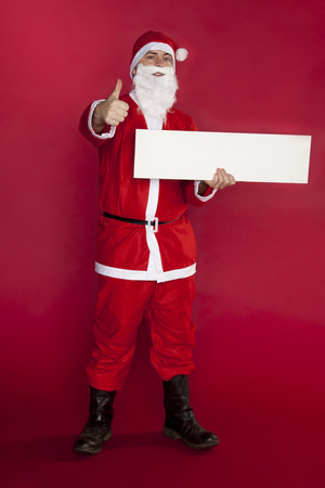 happy santa clause keeps a place for advertising, thumb up and copy space Imagens