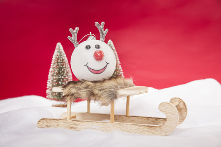 A reindeer bauble sitting on a sleigh, copy space